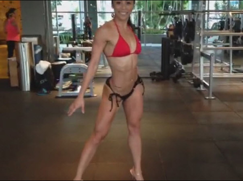bikini competitor pose practing in the gym