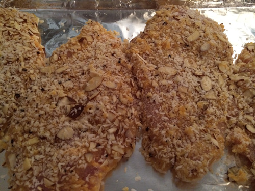 coconut almond crusted chicken breast on baking pan