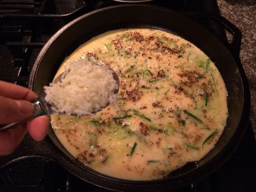 adding mozzarella cheese to a frittata